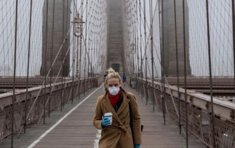 Woman in mask walks the Brooklyn Bridge during the COVID-19 pandemic. (Victor J. Blue/Stringer/Getty Images)