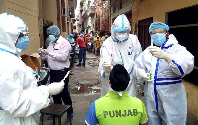 Health workers collect swab samples for COVID-19 testing, at a containment zone in Patiala. Photograph: PTI Photo