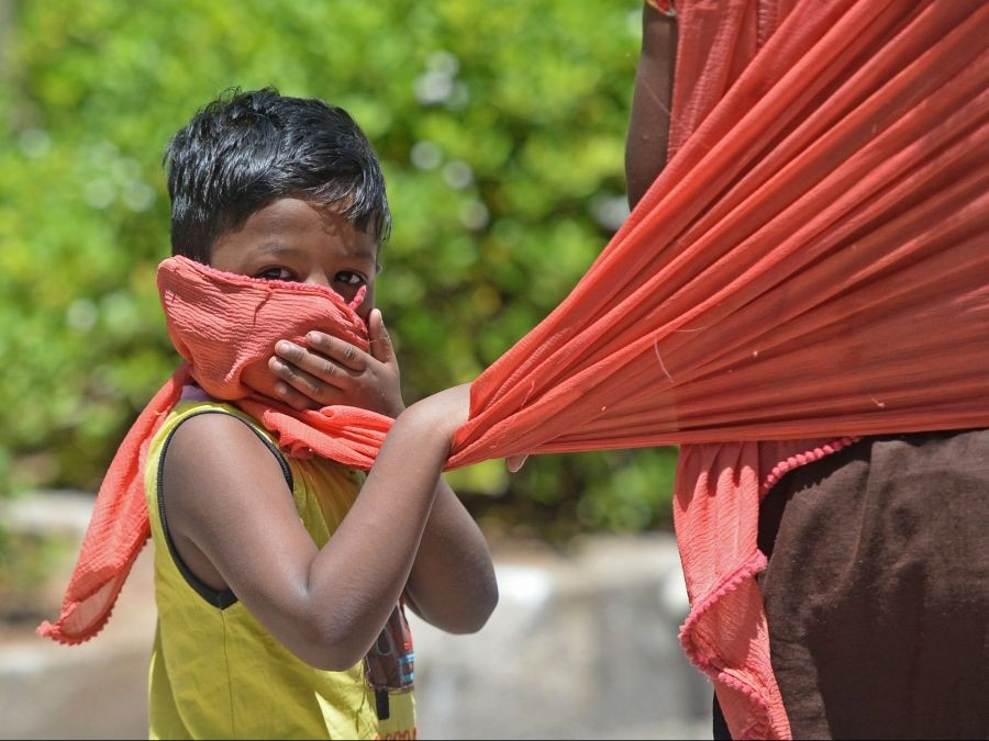 In this picture taken on July 8, 2020, a boy covers his face with the scarf of his mother as he walks along the road after the government eased a nationwide lockdown imposed as a preventive measure against the COVID-19 coronavirus, in Chennai, India.ARUN SANKAR / AFP via Getty Images