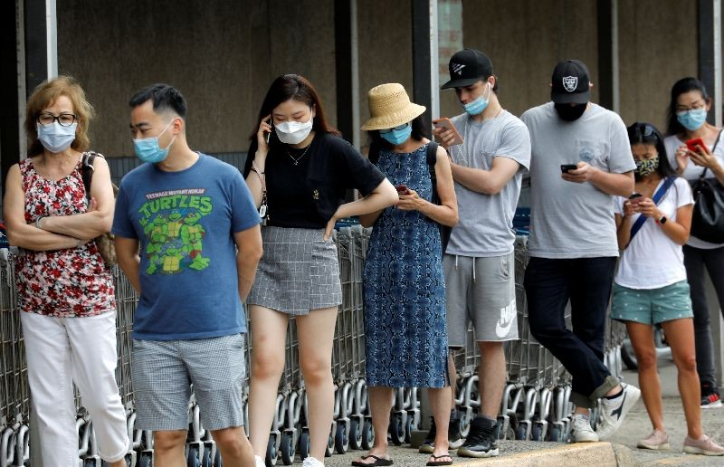 People wear protective face masks outside at a shopping plaza after New Jersey Governor Phil Murphy said he would sign an executive order requiring people to wear face coverings outdoors to prevent a resurgence of the coronavirus disease (COVID-19), in Edgewater, New Jersey, U.S., July 8, 2020. REUTERS/Mike Segar