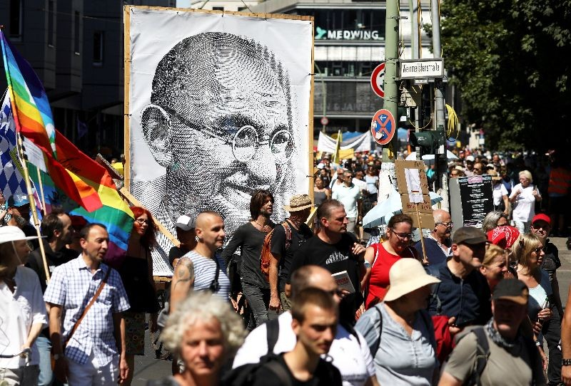 A portrait of Mahatma Gandhi is pictured as demonstrators march during a protest against the government's restrictions amid the coronavirus disease (COVID-19) outbreak, in Berlin, Germany, August 1, 2020. REUTERS/Christian Mang/File Photo