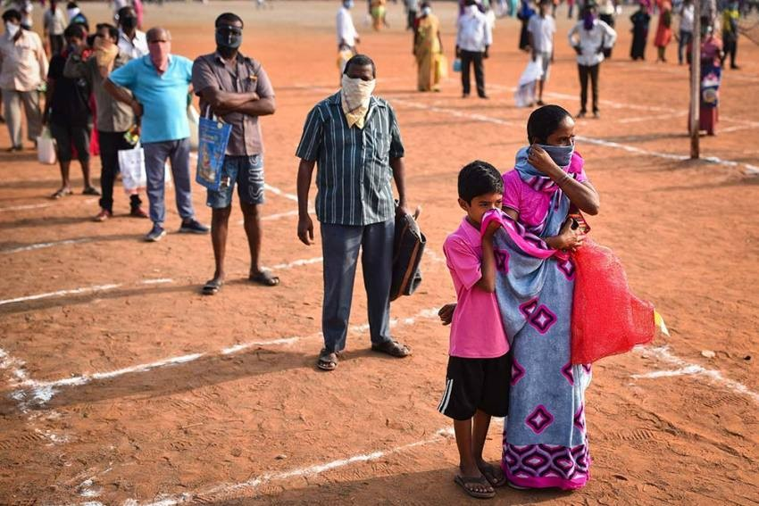 Locals maintain social distance as they stand in a queue to buy vegetables during day-2 of a nationwide lockdown, imposed in the wake of coronavirus pandemic, in Vijayawada. PTI Photo