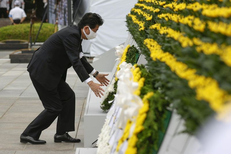 Japan's Prime Minister Shinzo Abe wearing a protective face mask, offers a wreath to the cenotaph for the victims of the 1945 atomic bombing, at Peace Memorial Park in Hiroshima, western Japan, August 6, 2020, on the 75th anniversary of the atomic bombing of the city. Kyodo/via REUTERS