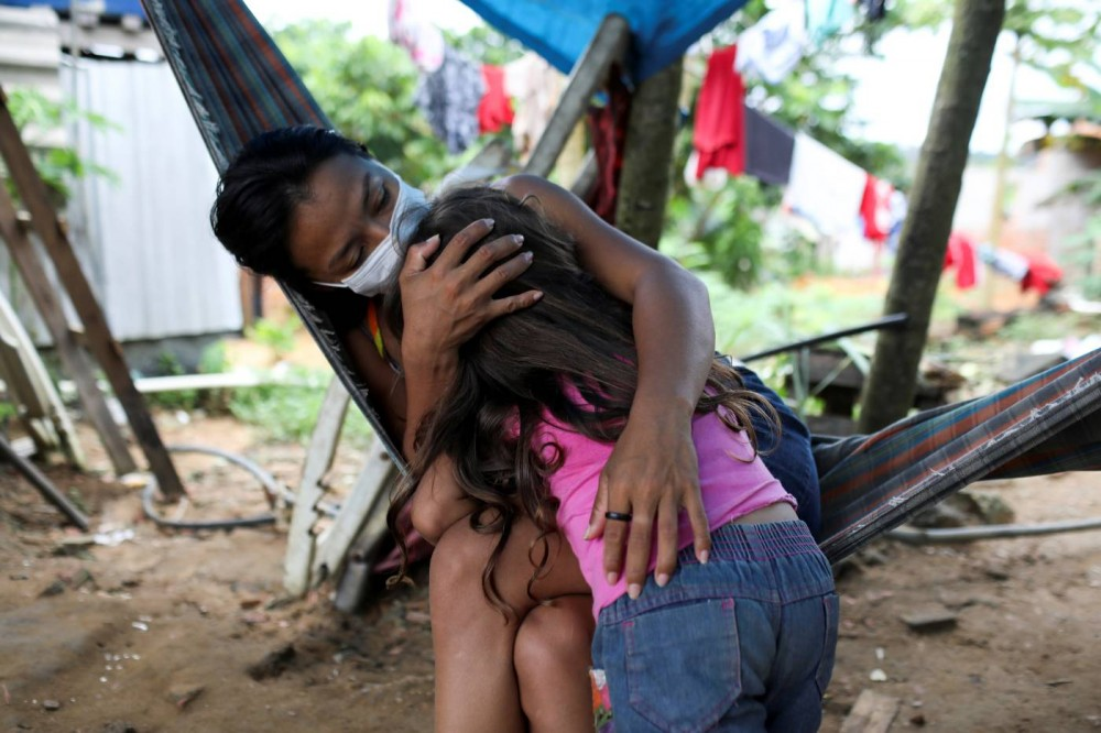 Vanderlecia Ortega dos Santos, 32, a nurse who has volunteered to provide the only frontline care protecting her indigenous community of 700 families from the COVID-19 outbreak, embraces her niece Maria Eduarda Ribeiro Ortega, 4, both of whom are from the Witoto tribe, an indigenous ethnic group, at Santos's home in Parque das Trios, during the coronavirus disease (COVID-19) outbreak, in the Taruma district, Manaus, Brazil, May 3, 2020. REUTERS/Bruno Kelly