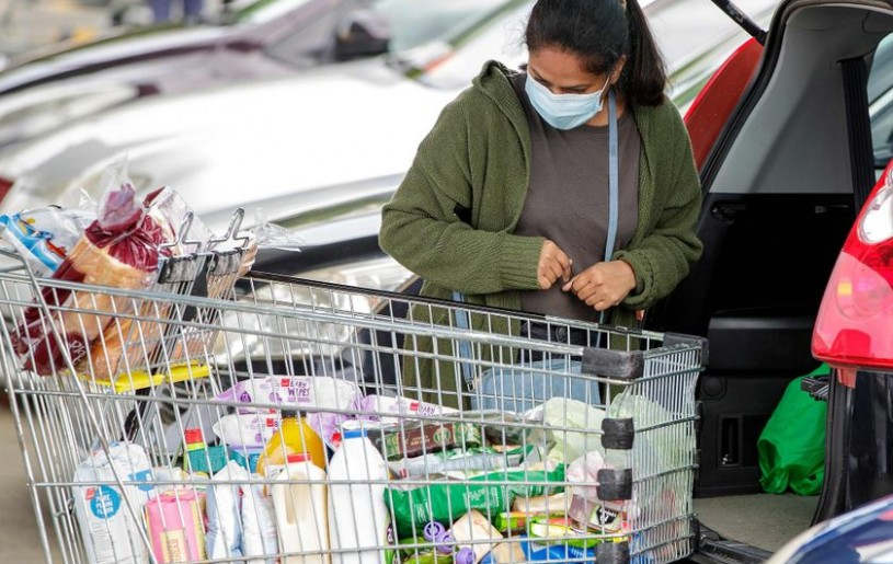 A face mask-clad shopper packs groceries in the suburb of Takapuna in Auckland, New Zealand on Aug. 12, 2020. DAVID ROWLAND / AFP via Getty Images