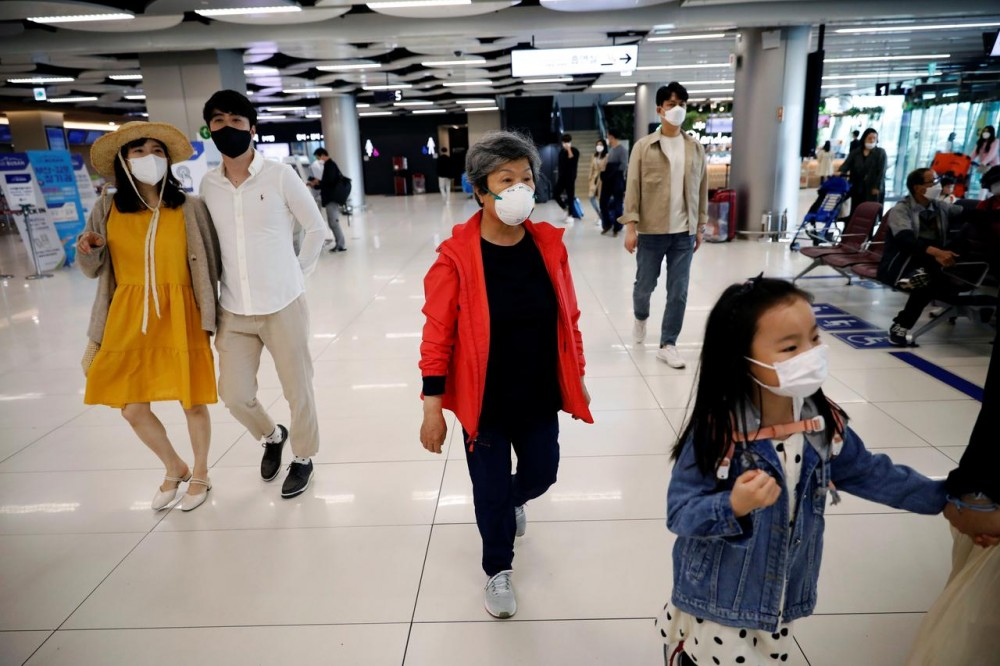 People wearing masks to avoid the spread of the coronavirus disease (COVID-19) arrive at Gimpo international airport in Seoul, South Korea, May 1, 2020. REUTERS/Kim Hong-Ji