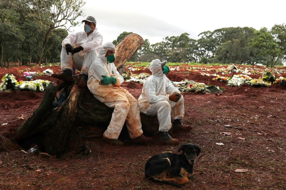 Gravediggers wearing protective suits rest between burials amid the outbreak of the coronavirus disease (COVID-19) at Vila Formosa cemetery, in Sao Paulo, Brazil. (REUTERS Photo)