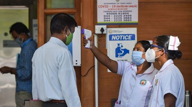 A staff nurse uses a thermal screening device on an employee at a hospital. Photograph: PTI Photo