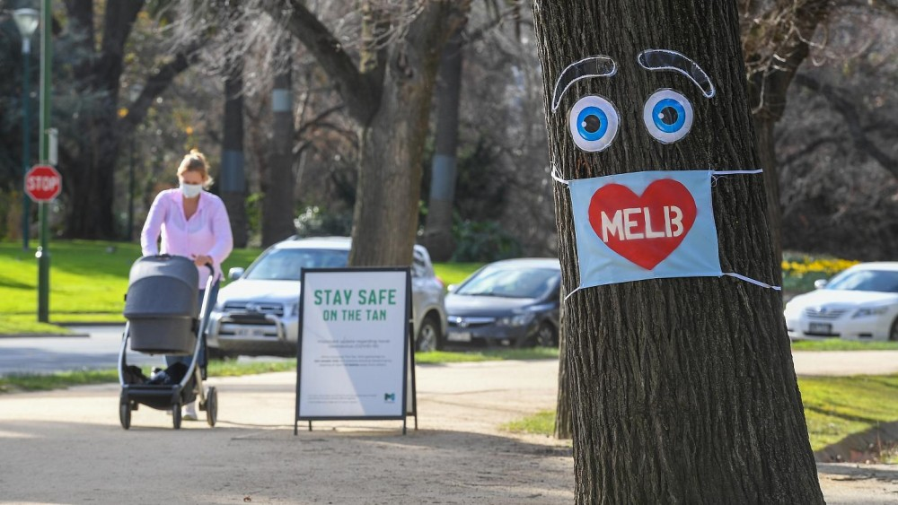 A woman pushes a pram past a large face mask pinned to a tree in Melbourne. AFP Photo