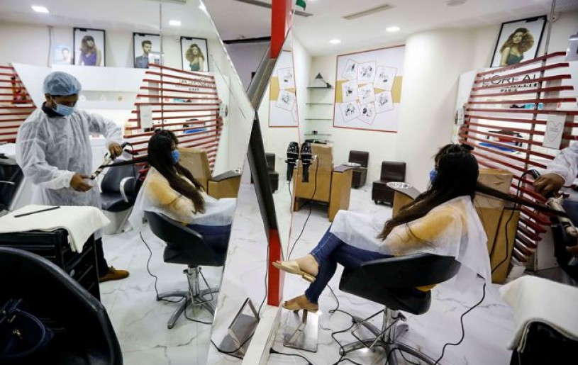 A beautician wearing protective gear tends to a customer inside a parlour at Gulmohar Park shopping mall in Ahmedabad. Photograph: Amit Dave/Reuters