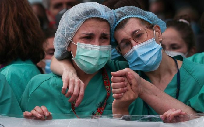 Health workers wearing protective face masks react during a tribute for their co-worker Esteban, a male nurse that died of the coronavirus disease, amid the coronavirus disease outbreak, outside the Severo Ochoa Hospital in Leganes, Spain. Photograph: Susana Vera/Reuters