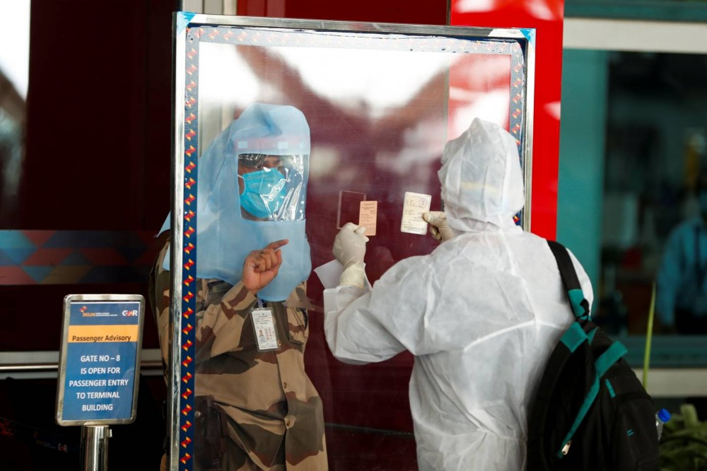 A member of the Central Industrial Security Force (CISF) checks the ID of a passenger through a glass shield, during an extended nationwide lockdown to slow the spread of the coronavirus disease (COVID-19), at Indira Gandhi International (IGI) airport, in New Delhi, India, May 25, 2020. REUTERS/Adnan Abidi