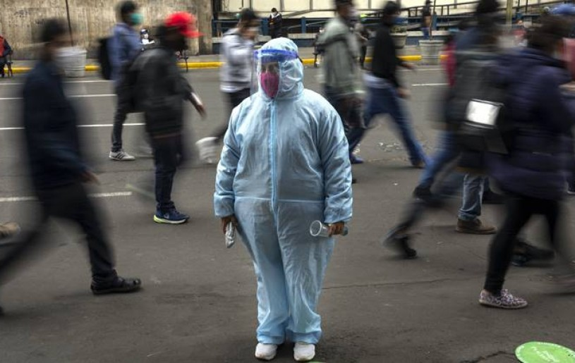 A woman waits outside a shop wearing protective gear due to the COVID-19 pandemic in downtown Lima, Peru. (AP Photo)
