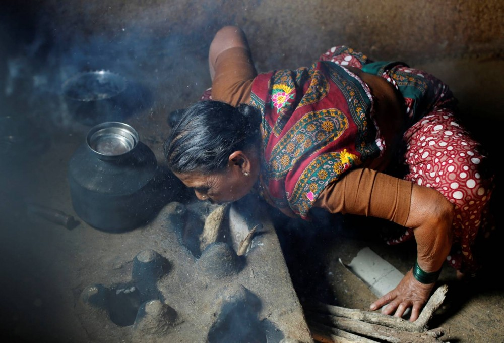 Kamal Keshavtupange, 60, lights a fire as she cooks food on a stove inside her house in Fangane village, India, February 15, 2017. REUTERS/Danish Siddiqui