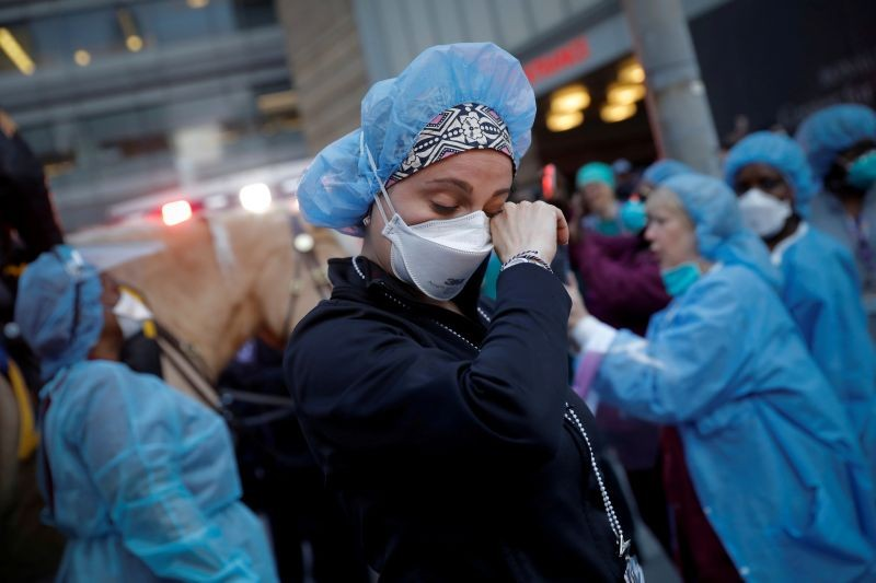 FILE PHOTO: A nurse wipes away tears as she stands outside NYU Langone Medical Center on 1st Avenue in Manhattan as New York police came to cheer and thank healthcare workers in New York City, New York, U.S., April 16, 2020. REUTERS/Mike Segar