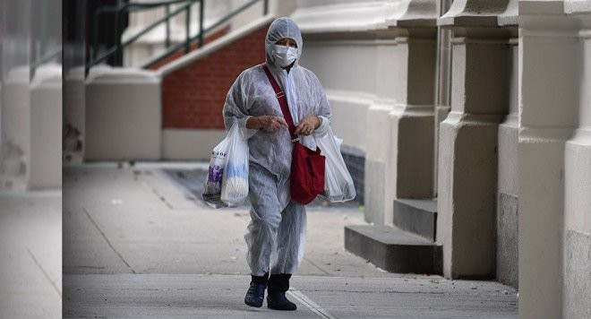 A person in a hazmat suit carries groceries on October 5, 2020 in the Brooklyn Borough of New York City. (Photo: AFP)