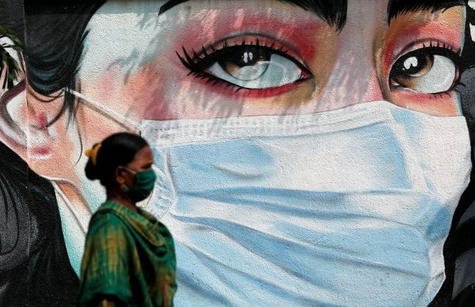 A woman walks past a graffiti of a girl wearing a protective mask amidst the spread of the coronavirus in Mumbai. Photograph: Francis Mascarenhas/Reuters