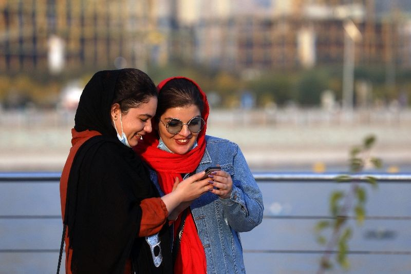 Iranian women use mobile phone, amid a rise in the coronavirus disease (COVID-19) infections, West of Tehran, Iran October 23, 2020. Picture taken October 23, 2020. Majid Asgaripour/WANA (West Asia News Agency) via REUTERS