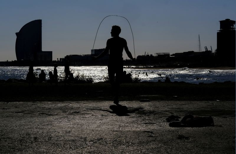 A man skips rope as he exercises at Barceloneta beach, after Spain's Catalonia region said it would allow gyms to reopen from Monday amidst the coronavirus outbreak, in Barcelona, Spain November 22, 2020. REUTERS/Nacho Doce