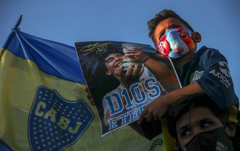 A kid sitting on the shoulders of a man holds a poster of Maradona in front of the Casa Rosada presidential palace, as people gather to mourn the death of soccer legend Diego Armando Maradona, in Buenos Aires, Argentina, November 26, 2020. REUTERS/Ricardo Moraes