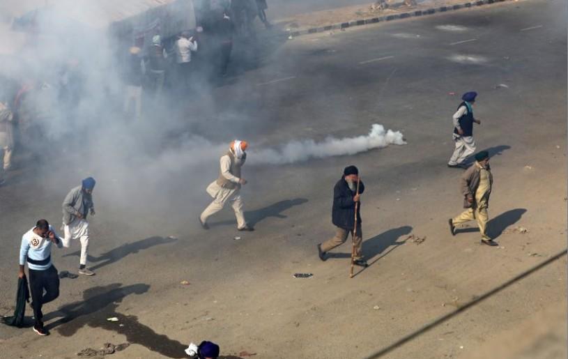 People move away from tear gas as farmers protest against the newly passed farm bills at Singhu border near Delhi, India, November 27, 2020. REUTERS/Anushree Fadnavis