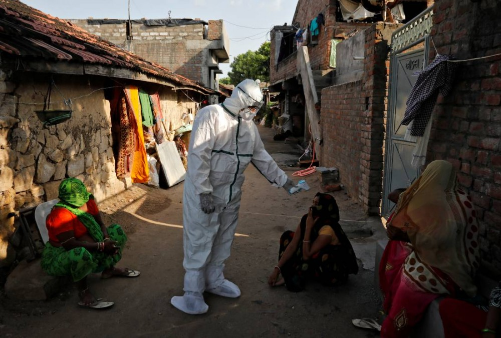 A healthcare worker wearing personal protective equipment (PPE) checks the temperature of a woman sitting outside her house in an alley during a door-to-door survey for the coronavirus disease (COVID-19), in Jakhan village in the western state of Gujarat, India, September 22, 2020. REUTERS/Amit Dave