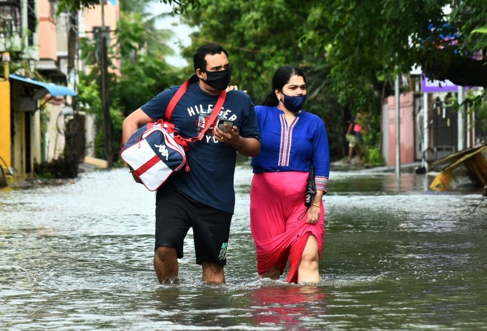 People wade through a water-logged road after Cyclone Nivar's landfall, in Chennai, India, November 26, 2020. REUTERS/P. Ravikumar