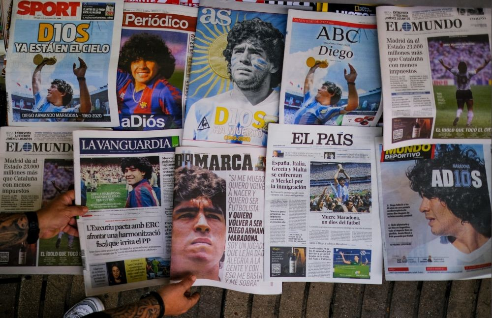 A worker arranges the front pages of Spanish newspapers paying tribute to late soccer legend Diego Maradona at Las Ramblas, in Barcelona, Spain November 26, 2020. REUTERS/Nacho Doce