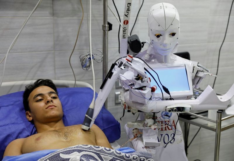 A volunteer is examined by Cira 3, a remote-controlled robot that runs tests on suspected coronavirus disease (COVID-19) patients to limit the human exposure to the virus, amid a second wave of infections in Tanta, Egypt, November 18, 2020. Picture taken November 18, 2020. REUTERS/Mohamed Abd El Ghany
