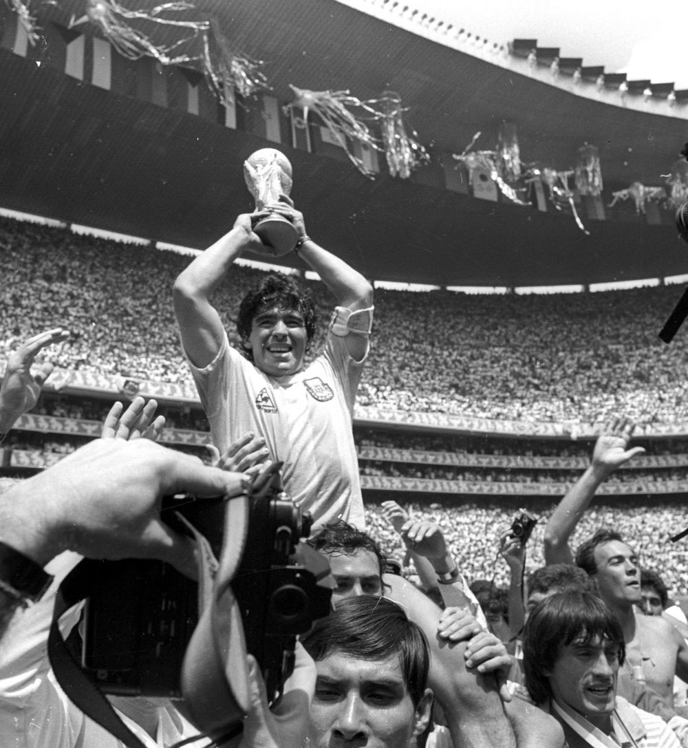 Argentine star Diego Maradona holds up the World Cup trophy as he is carried off the field after Argentina defeated West Germany 3-2 to win the World Cup soccer championship in Mexico City June 29, 1986. REUTERS/Gary Hershorn/File Photo
