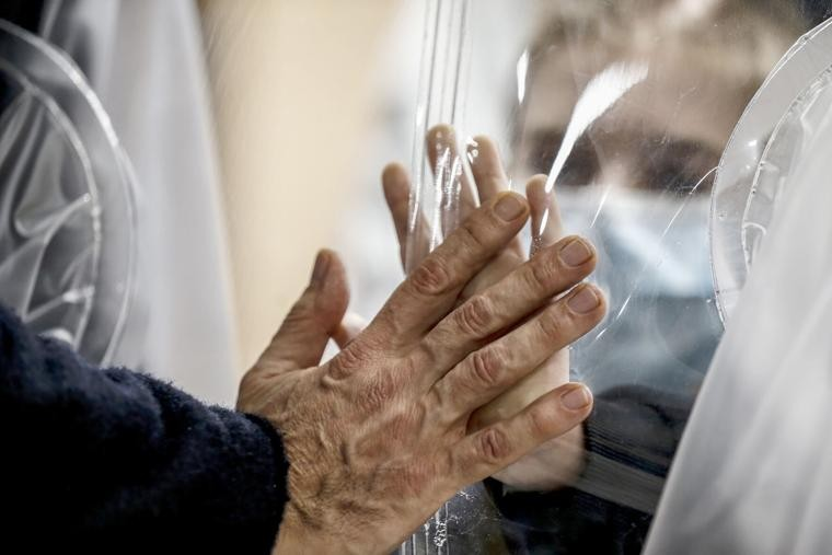 FILE - In this Dec. 22, 2020, file photo, relatives touch each other's hand through a plastic film screen and a glass to avoid contracting COVID-19 at the San Raffaele center in Rome ahead of Christmas. All most people wanted for Christmas after this year of pandemic was some cheer and togetherness. Instead many are heading into a season of isolation, grieving lost loved ones, experiencing uncertainty about their jobs or confronting the fear of a potentially more contagious variant of the coronavirus.