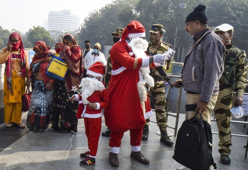 New Delhi: A volunteer dressed as Santa Claus distributes face masks during a COVID-19 awareness drive, in New Delhi, Wednesday, Dec 23, 2020. (PTI Photo/Shahbaz Khan)