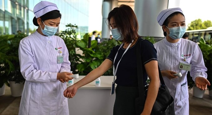 A medical worker gestures after taking the temperature of an AFP photojournalist at Tongji Hospital in Wuhan. Photo: AFP