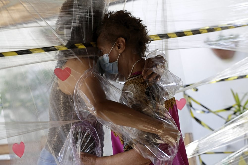 FILE - In this Jan. 6, 2021, file photo, Maria Amelia, right, hugs her niece Flaviana Silva through a plastic barrier during a visit to the Casa Clara home for the elderly in Brasilia, Brazil. The global death toll from COVID-19 has topped 2 million. (AP Photo/Eraldo Peres, File)