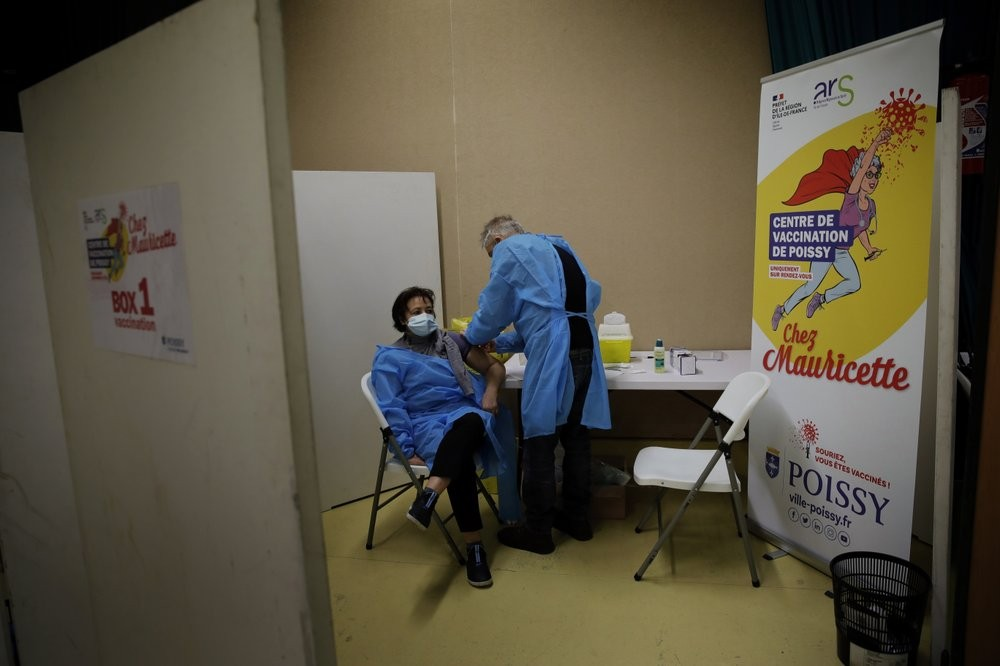 FILE - In this Jan. 8, 2021, file photo, a nurse, Ines receives a Pfizer-BioNTech COVID-19 vaccine at a coronavirus vaccine center in Poissy, France. The global death toll from COVID-19 has topped 2 million. (AP Photo/Christophe Ena, File)