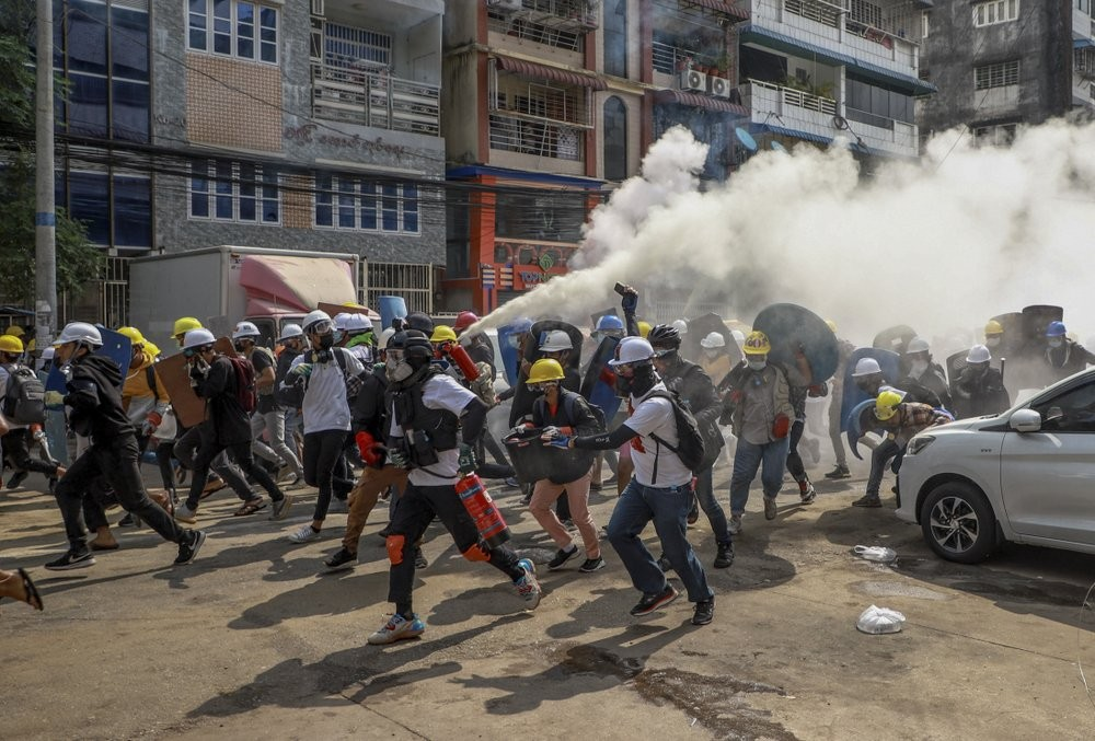 FILE - In this March 3, 2021, file photo, anti-coup protesters run as one of them discharges a fire extinguisher to counter the impact of tear gas fired by riot policemen in Yangon, Myanmar. The escalation of violence in Myanmar as authorities crack down on protests against the Feb. 1 coup is adding to pressure for more sanctions against the junta, as countries struggle over how to best confront military leaders inured to global condemnation. (AP Photo/File)