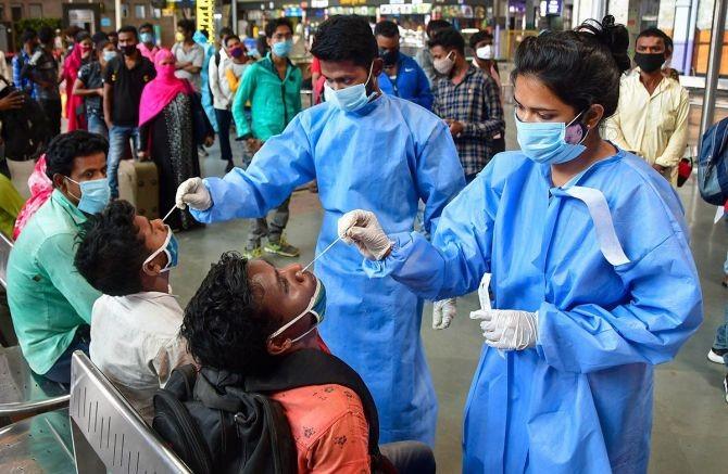Health workers take swab samples of passengers at Chhatrapati Shivaji Maharaj Terminus Railway Station, amid spike in Covid-19 cases, in Mumbai. Photograph: PTI Photo