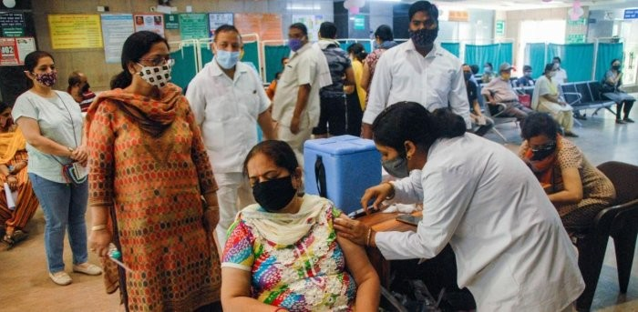 A health worker administers Covid-19 vaccine doses to people in Noida. Credit: PTI photo