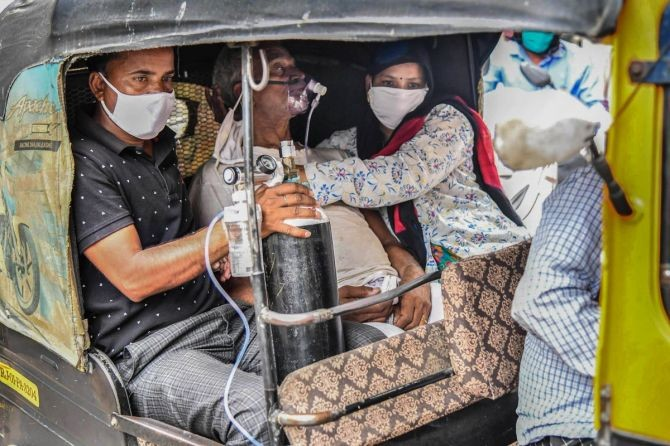 A COVID-19 patient on oxygen support being taken in an auto rickshaw to a hospital for treatment, in Ajmer, on Sunday. Photograph: PTI Photo