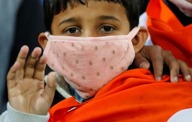 A boy wears a mask as he waits for the start of the first One-day International cricket match between India and South Africa amid coronavirus fears at Himachal Pradesh Cricket Association Stadium in Dharamsala India