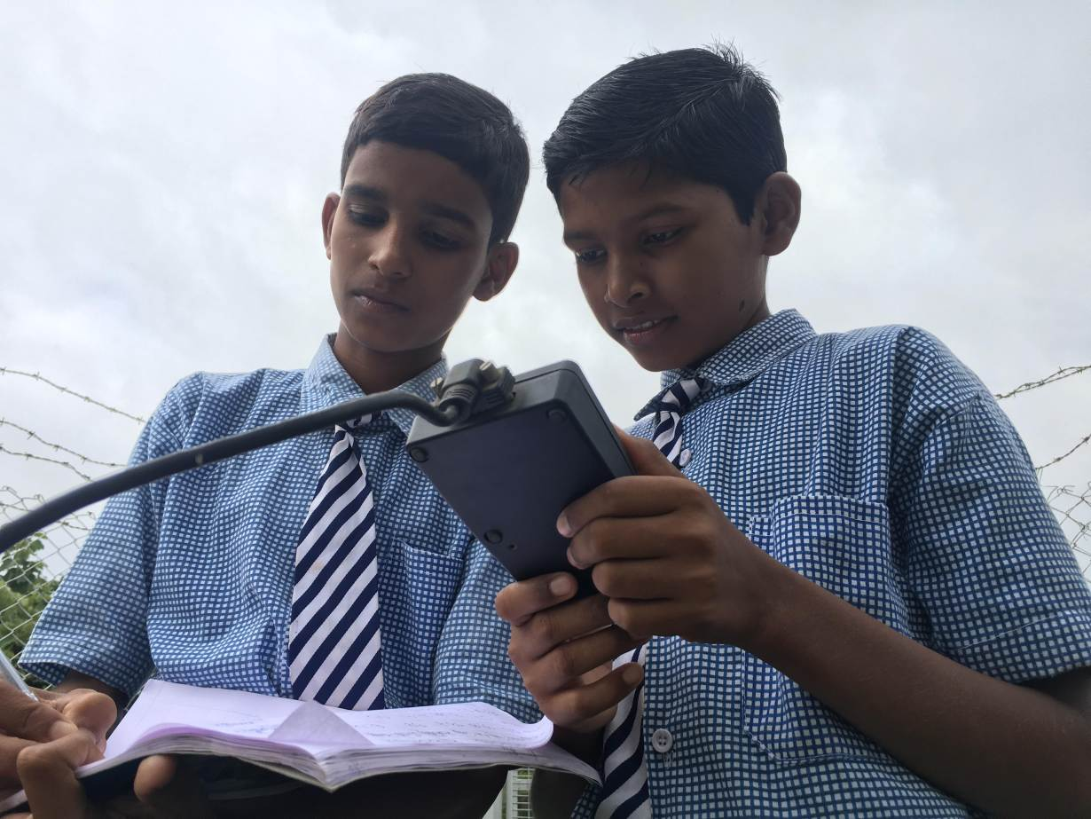 Vamshi Voggu and Gurulingam Goud, ninth grade students at the Kothapally village high school, check weather readings at the automatic weather station on their school premises in Kothapally, India, on July 31, 2019. Thomson Reuters Foundation/Roli Srivastava
