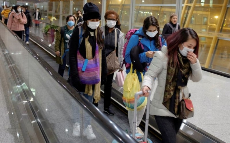 People wear face masks as they arrive at Beijing Capital International Airport in Beijing, January 25, 2020. REUTERS/Thomas Peter