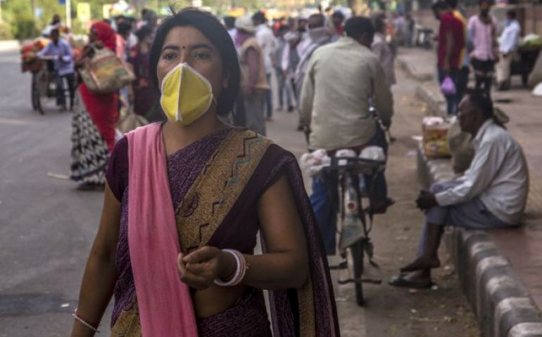 An Indian woman covering her face with a mask walks in a crowded market place, as nationwide lockdown continues over highly contagious novel coronavirus on March 26, 2020 in New Delhi, India. India is under a 21-day lockdown to fight the spread of Covid-19 infections and while the security personnel on the roads are enforcing the restrictions in many cases by using force, the workers of country's unorganized sector are bearing the brunt of the curfew-like situation. According to the international labour org