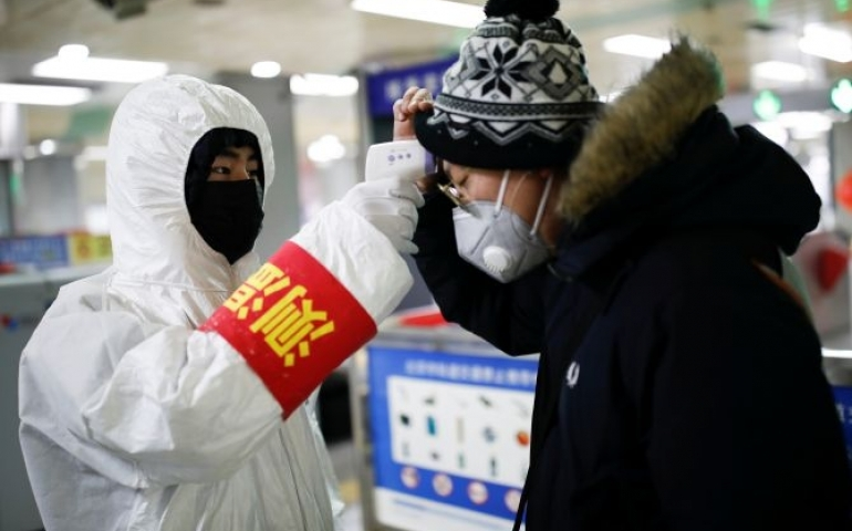 A staff member checks the temperature of a passenger entering a subway station, as the country is hit by an outbreak of the new coronavirus, in Beijing, China. Photograph: Carlos Garcia Rawlins/Reuters